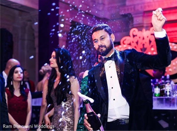Indian groom opening champagne bottle