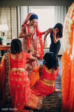 Indian bride getting help to put on her jewelry