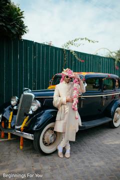 Elegant indian groom posing next to wedding car