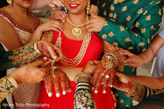 Indian bride being helped with her jewelry.
