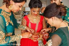 Joyful Indian bride getting ready for wedding ceremony.