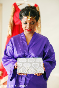 Lovely Indian bride holding card capture.