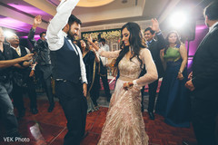 Joyful indian wedding couple dancing
