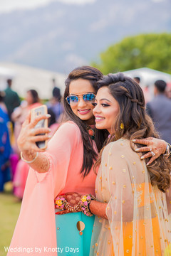 Lovely Indian bride with friend at mehndy pre-wedding celebration.