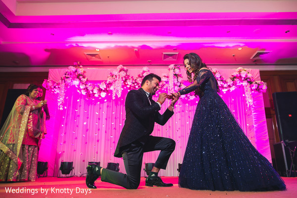 Indian groom putting bride the wedding ring at a performance.