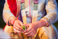 Closeup capture of Indian groom holding grass for wedding ritual.