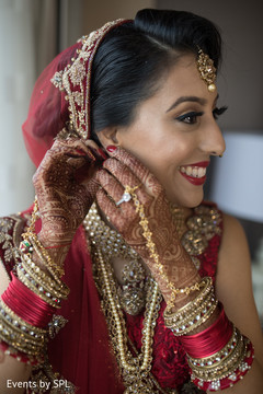Indian bride putting jewelry on