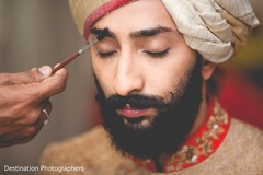 Indian groom being helped to get ready