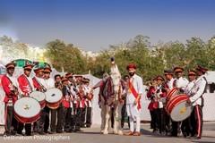 Indian groom posing with baraat horse
