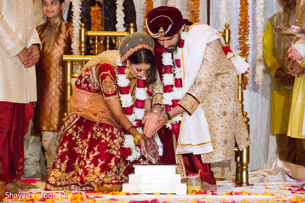 Indian bride and groom throwing the rice together in to fire.