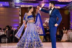 Charming Indian bride and groom enjoying wedding dance.
