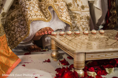 Indian bride touches with toe seven nuts or betel.