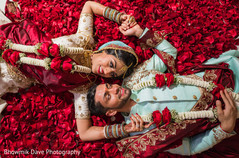 Romantic Indian bride and groom laying on red rose petals capture.