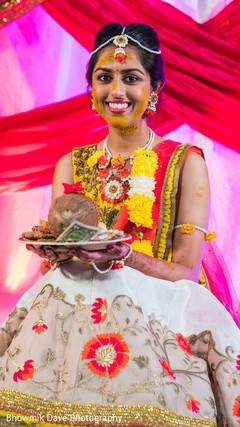 Maharani holding the coconut at haldi ceremony.