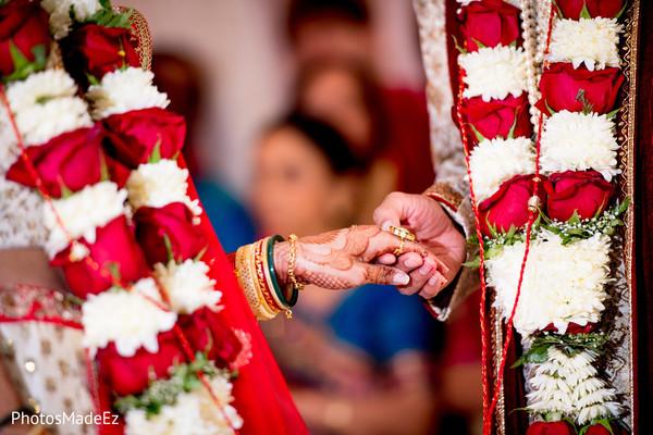 Indian groom taking hand of bride on wedding ceremony