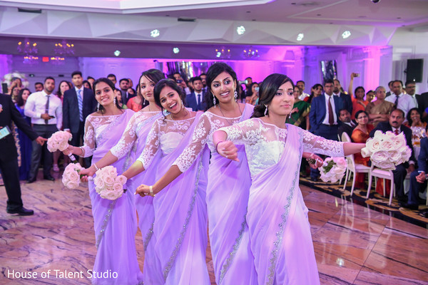 Indian bridesmaids  dancing on wedding reception party.