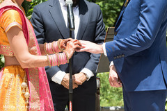 Indian bride putting wedding ring to groom capture.