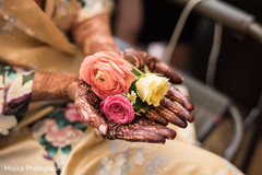 Lovely flowers held by maharanis hands with amazing mehndi art.