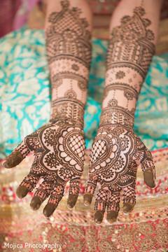 Indian bride's hands with mehndi art capture.
