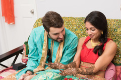 Indian bride and groom admiring the mehndi art on bride's hands.