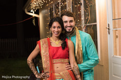 Joyful couple posing with their mehndi outfits.