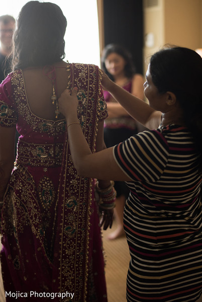 Indian bride being helped to get dress for reception.