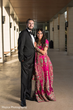 Gorgeous Indian bride and groom posing with their wedding reception outfits.