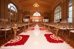 Indian wedding aisle petals and statues decorations.