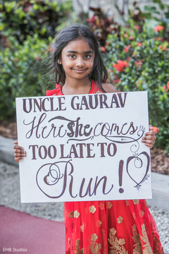 Lovely Indian guest holding a sign for groom.