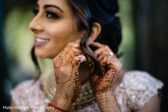 Indian bride putting earrings on capture