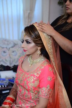 Indian bride being helped to put her Ghoonghat.