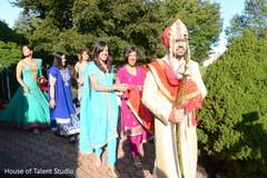 Indian bridesmaids following groom to baraat celebration.