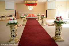 Indian wedding aisle flowers and draping decorations.