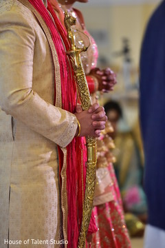 Closeup capture of Indian groom holding his sword.