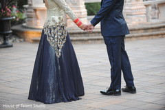 Dazzling Indian bride and groom holding hands.