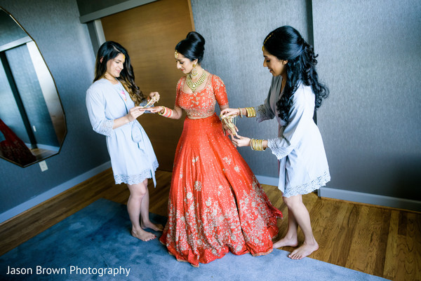Indian bride being helped to get ready