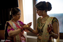 Indian bride being helped with jewelry.