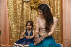 Indian bride showing mehndi art with flower girl.