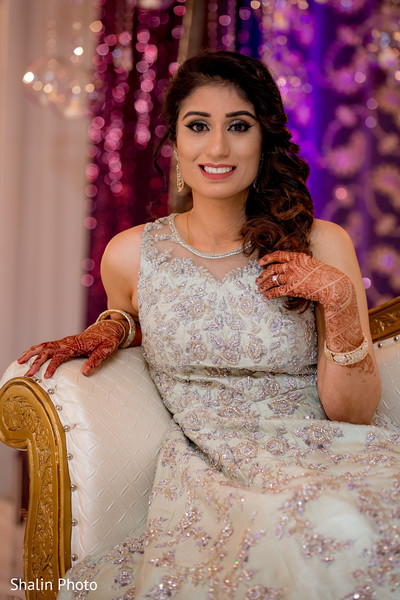 Ravishing indian bride posing on her wedding reception outfit.