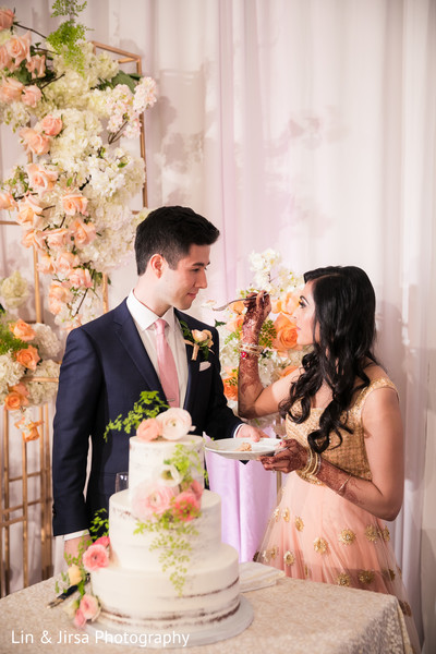 Sweet indian couple cutting their wedding cake