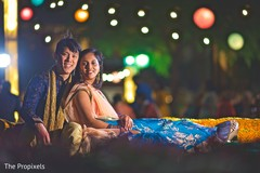 Charming Indian couple taking a portrait under the light decoration.