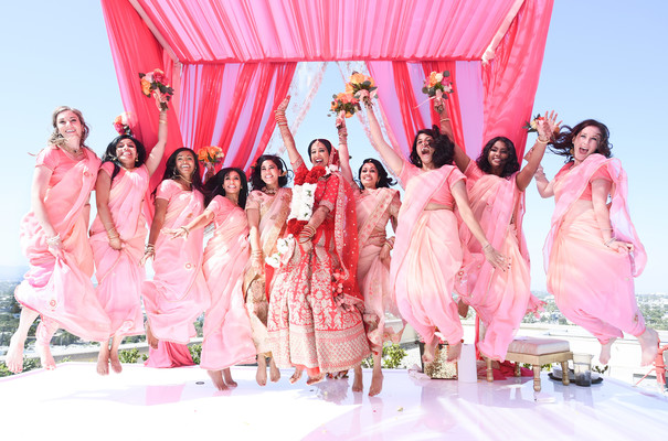 Joyful Indian bride with bridesmaids on their wedding ceremony outfits.
