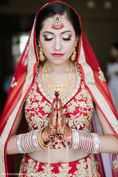Lovely indian bride in a gold and red lengha