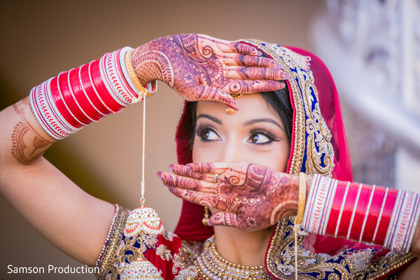 Radiant Indian bride showing the mehndi designs prior to the ceremony.