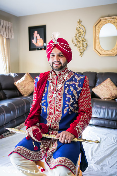 Elegant Indian groom posses wearing the sherwani and the kirpan.