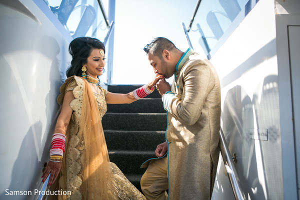 Indian groom kisses the stunning maharani's hand.