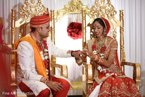 Indian bride purrint the wedding band to groom capture.