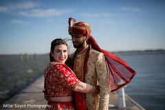 Indian groom stares at his beautiful wife as the photo shoot continues.