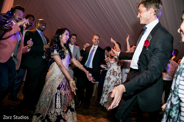 Indian bride and groom dancing at wedding reception.