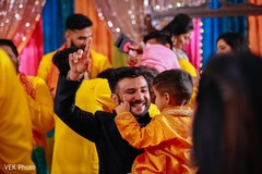 Kid dances with the groom at the Indian wedding rituals.